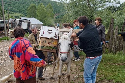 A family from Bishnica loads family parcels into their van